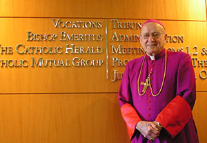 Bishop Bullock stands next to the sign for the office of