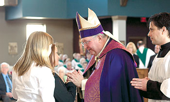 Bishop Robert C. Morlino receives candidate Kimberly Kazort during the Rite of Election and Call to Continuing Conversion at St. John the Baptist Church in Waunakee on March 13, 2011. (CH file photo)