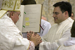 Bishop Robert C. Morlino and candidate David Johannes join hands as the latter says his vows to become a transitional deacon.