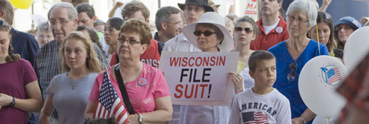 A woman holds a 'Wisconsin File Suit' sign at the Stand Up Rally for Religious Freedom June 8 at the federal courthouse in Madison. Click for more photos from the rally. (Catholic Herald photo/Kat Wagner)