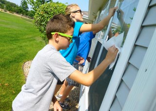 Members of the Love Begins Here mission trip spend time cleaning windows. (Contributed photo)