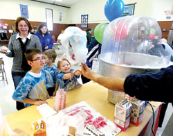 A happy student at Blessed Trinity School in Dane receives a cotton candy treat during a school carnival as part of Catholic Schools Week activities Thursday, Jan. 30.